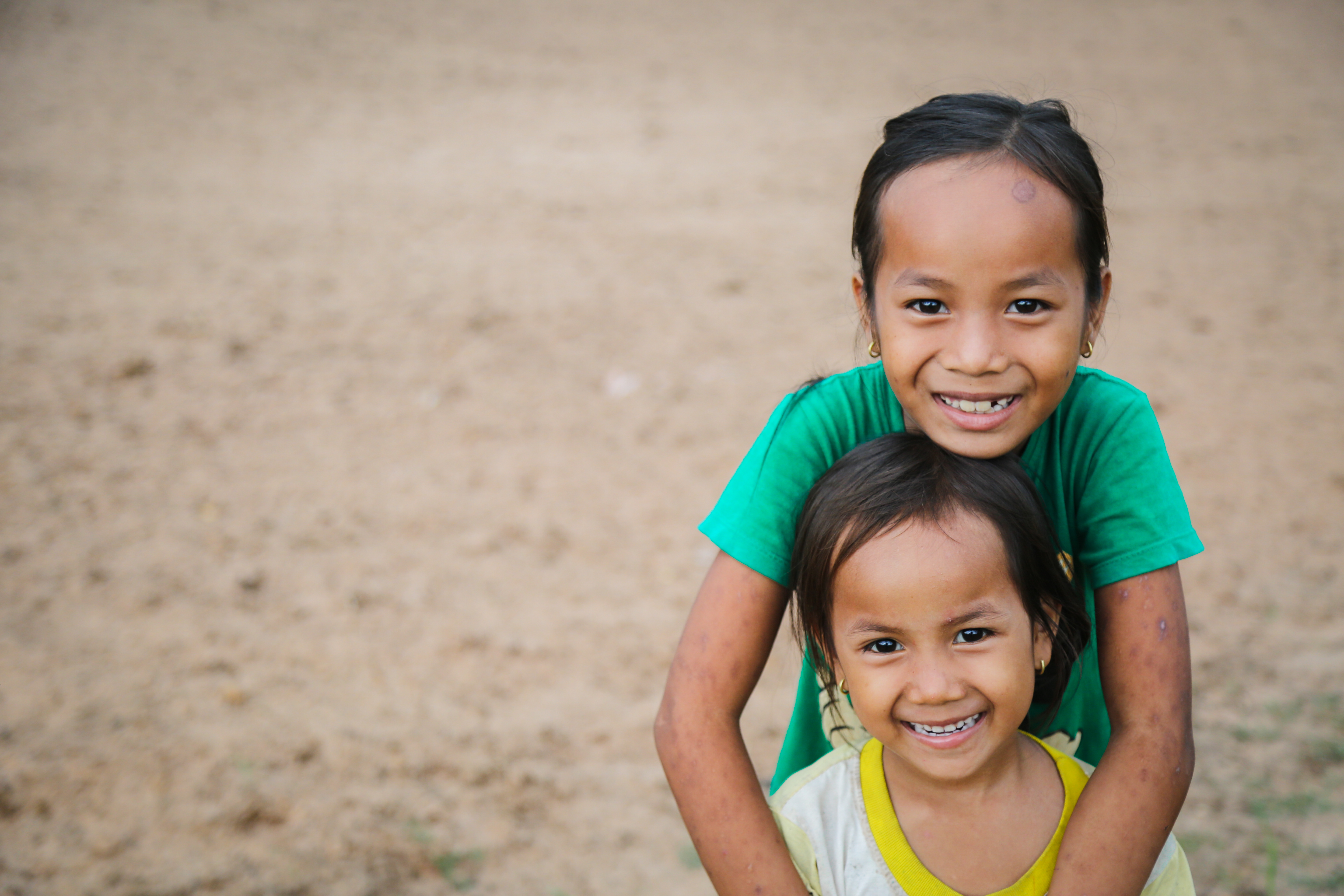 Two sisters hug out the front of their home in Cambodia