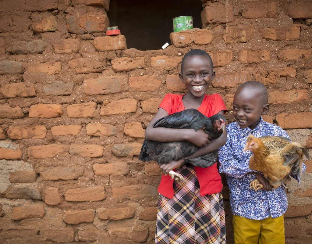 Nduku (10) and her brother Muthiani (6) hold chickens given to them by ChildFund in Makueni County, Kenya.