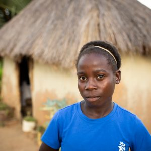 A young girl outside her home in rural Zambia